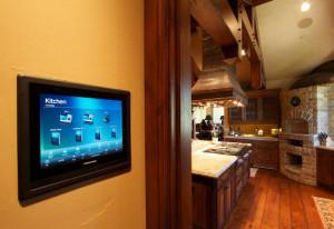 """Cette installation de cuisine, par Lifestyle Electronics, montre une GUI personnalisée dans un écran tactile mural. Si vous regardez au plafond, vous verrez également un haut-parleur """"architectural""""."""