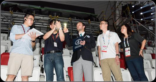 Le juge du GUINNESS WORLD RECORDS (au centre) vérifie la luminosité de l'image projetée en présence de témoins indépendants et d'Adrian Goh, directeur général d'Hexogon Solution (deuxième à droite).